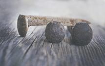 three rusty nail spikes