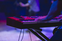 hands on a keyboard at a concert