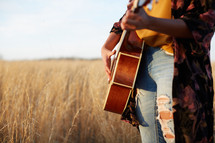 a woman standing in a field playing a guitar