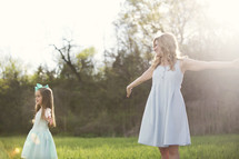 mother and daughter dancing in the sunlight