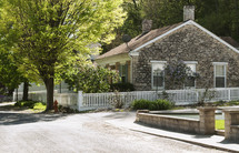 stone house with white picket fence