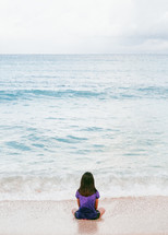 a girl sitting on a beach looking out at the ocean