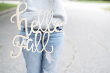woman holding a hello fall sign
