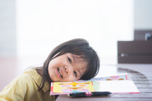 The little girl does her homework at her desk at home