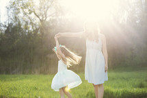 mother and daughter dancing outdoors in sunlight