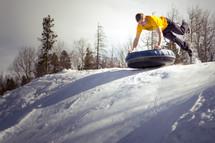 a man tubbing on a snowy hill