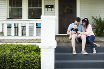 Young mom and dad sitting on the front steps of a house with their son.