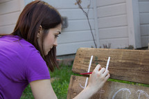 a teen girl painting on a bench