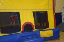 boys jumping in a bouncy house at a festival