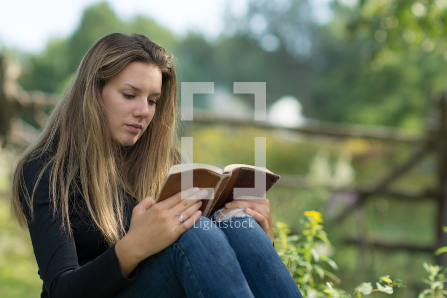 Girl reading a bible outside.