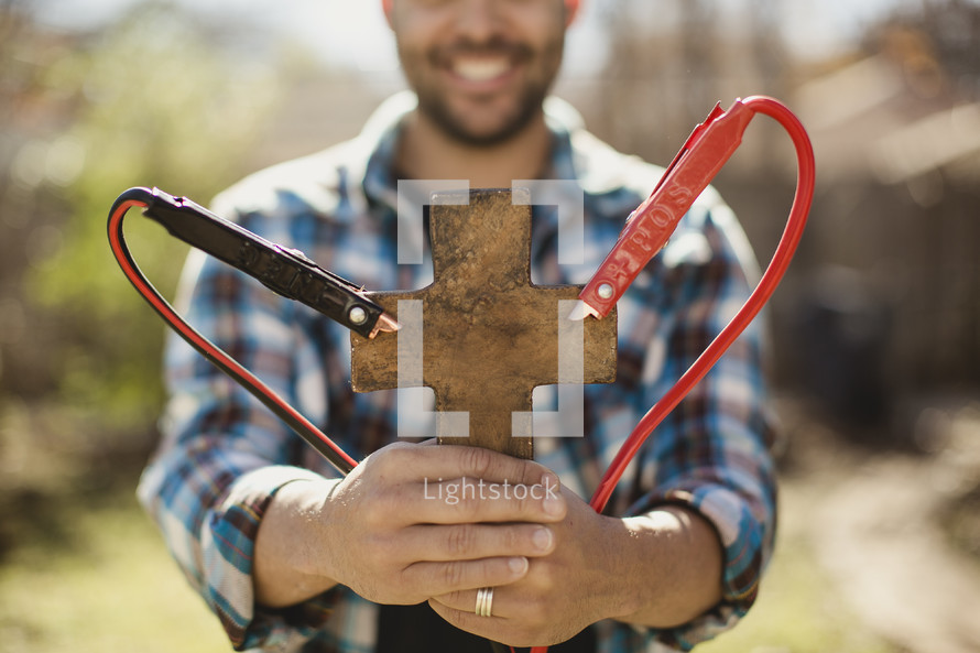 Smiling man holding cross with jumper cables attached.