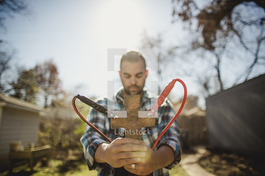 Man with eyes closed and head bowed holding clay cross with jumper cables attached.