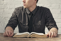 A man in front of an open Bible