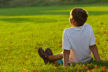 Boy sitting outside alone in sunshine