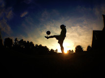 silhouette of a girl juggling a soccer ball