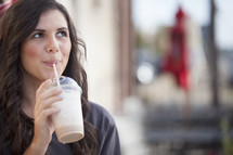 woman drinking an iced coffee