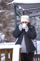 a woman standing on a snow covered deck drinking hot cocoa