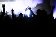 silhouettes of an audience with raised hands