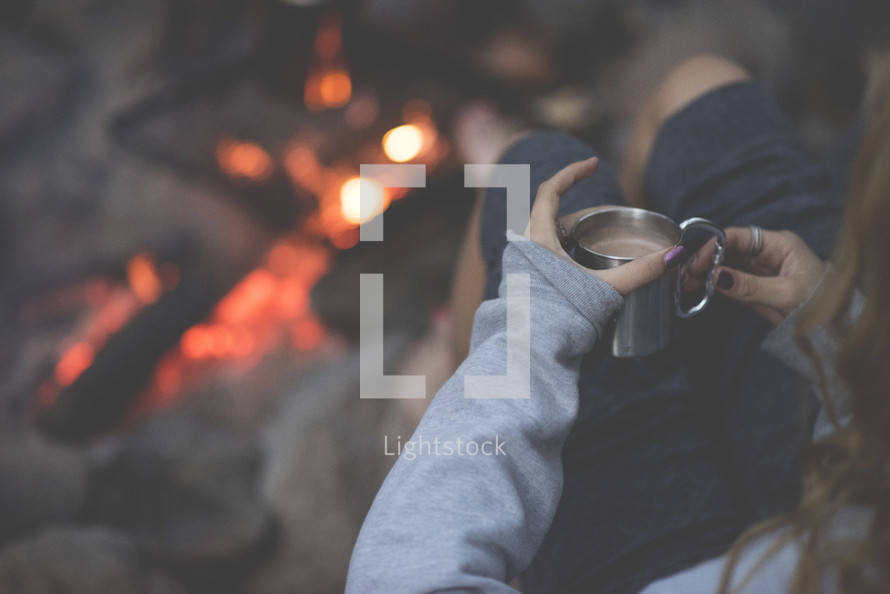 woman holding a mug of hot cocoa sitting by a campfire