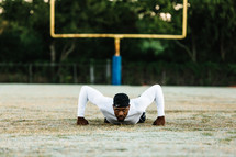 a man doing pushups on a sports field