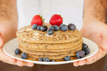 Hands holding a plate of almond pancakes covered in berries.
