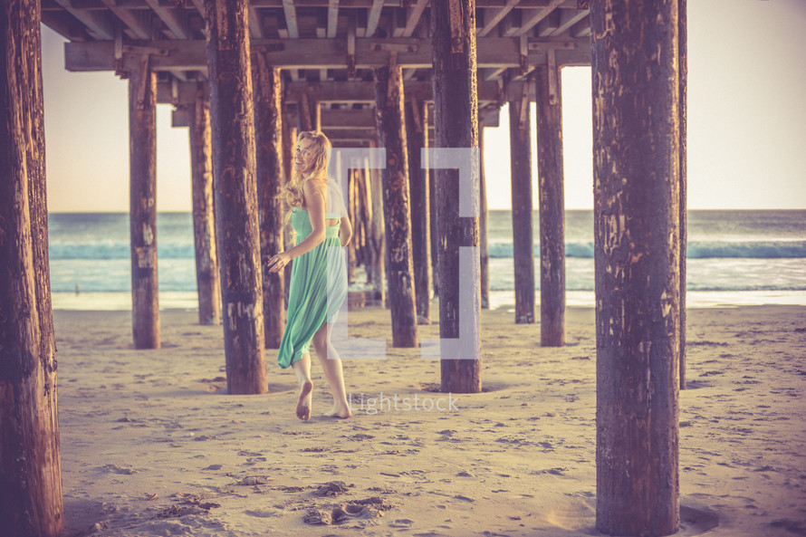 A woman walking in the sand under a pier.