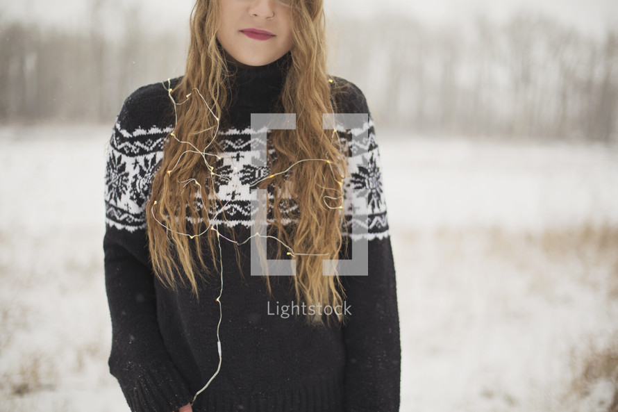 a young woman standing in the snow with Christmas lights
