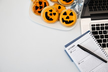 Halloween cookies on a plate next to a laptop computer