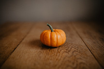 one tiny pumpkin on table