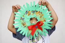 a child holding a handmade wreath