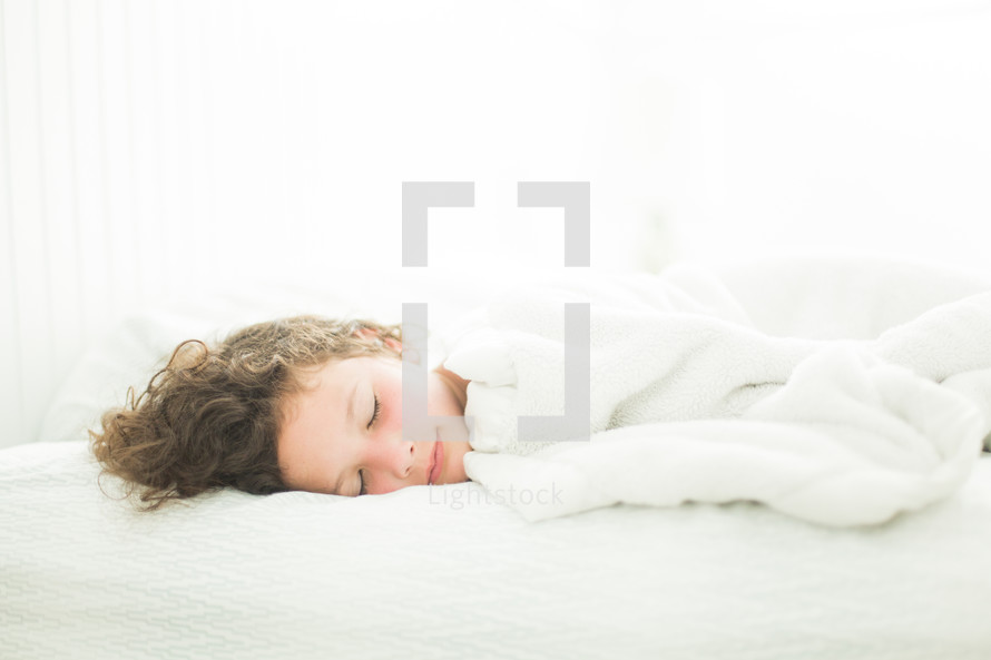 Child asleep in white bedroom with sun-kissed cheeks.