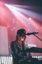 spotlights on a keyboardist on stage