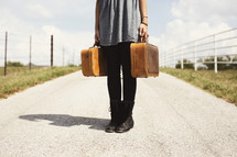woman standing in the middle of a road holding luggage.