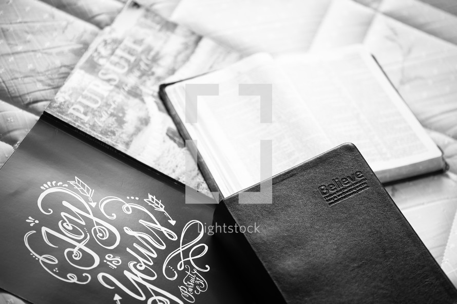 stack of journals and Bible on a bed