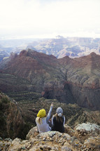 women sitting on the side of a mountain looking out at canyons