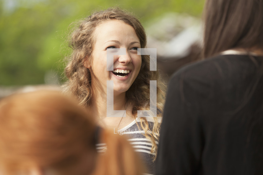 Teenage girl laughing with a friend.
