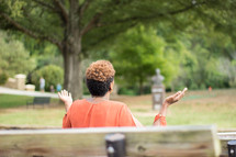 a woman sitting on a park bench with raised hands praying to God