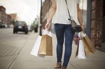 a woman walking down a sidewalk carrying shopping bags