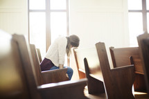 a woman sitting in a church pew with her head held down in prayer.