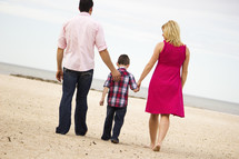 Back view of a father, son and mother walking on beach