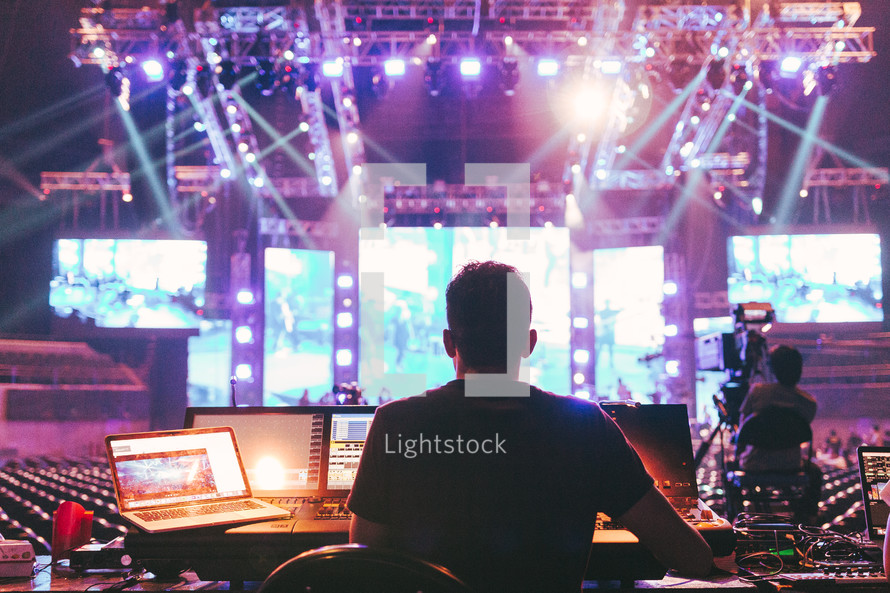 a man behind a sound booth at a concert