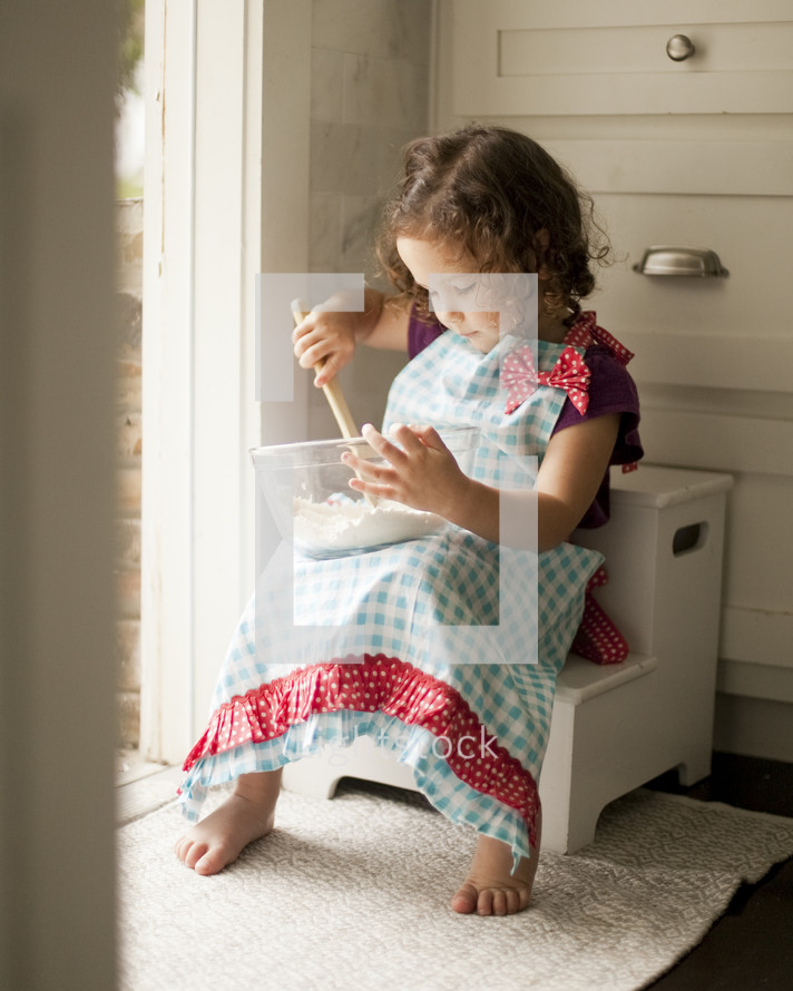 Little girl in apron baking in kitchen