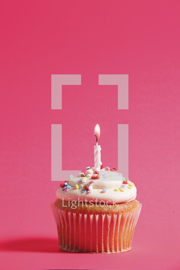 cupcake and candle against a fuchsia background