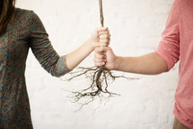 man and woman holding on to roots