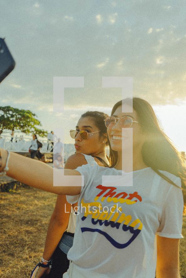 teen girls taking a selfie on a beach