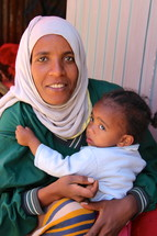Ethiopian muslim woman holding her toddler daughter  [For more search Ethnic Face Smile].