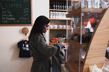 woman paying at a coffee shop