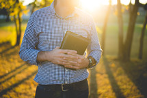 a man holding a Bible outdoors