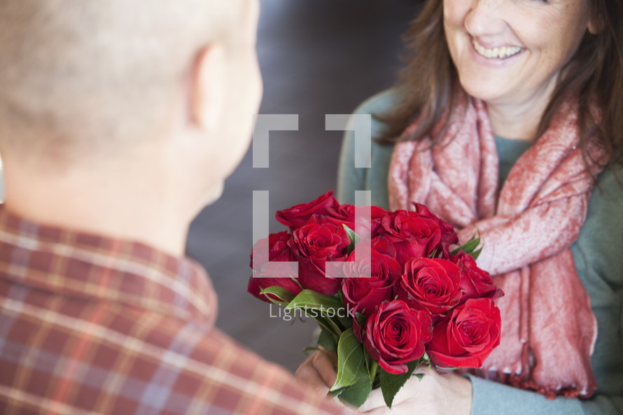 woman  receiving roses from her husband