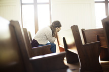 a woman hiding her face sitting in a church pew